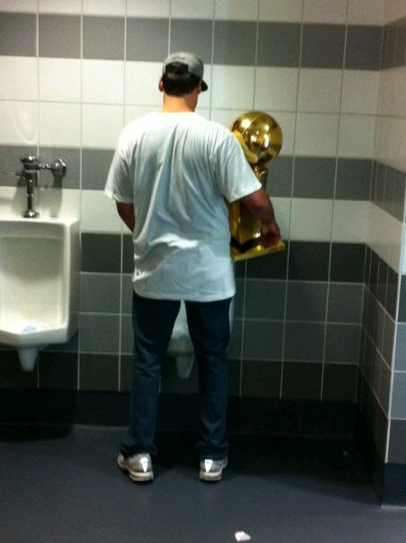 No pics of the billboard yet, so heres Mark Cuban at a urinal with the NBA championship trophy.